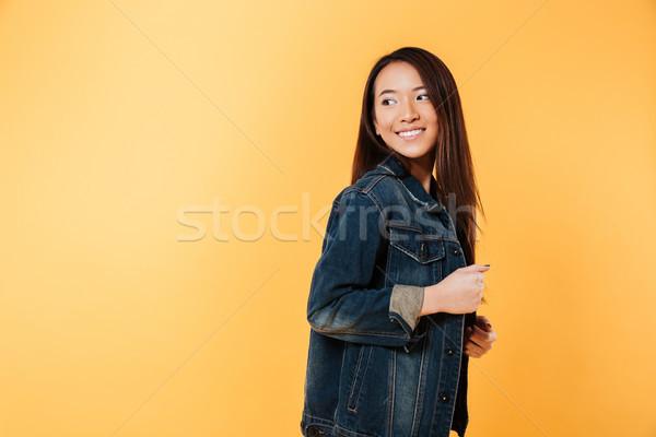 Vue de côté heureux asian femme denim veste Photo stock © deandrobot