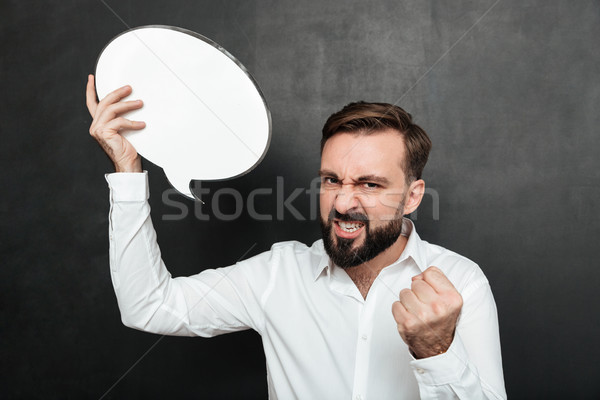 Close up photo of successful man holding blank speech bubble enc Stock photo © deandrobot