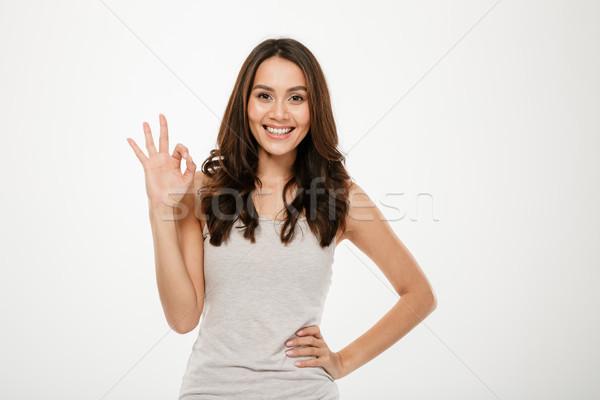 Boldog barna hajú nő kar csípő mutat Stock fotó © deandrobot