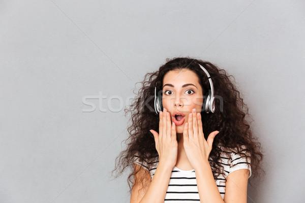 Portrait of brunette mixed-race woman listening to music via wir Stock photo © deandrobot