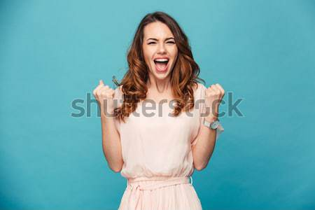 Portrait of an excited pretty girl dressed in sweater screaming Stock photo © deandrobot