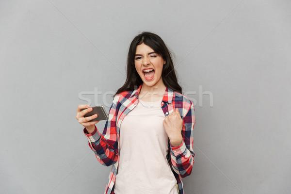 érzelmes fiatal hölgy játék játékok mobiltelefon Stock fotó © deandrobot