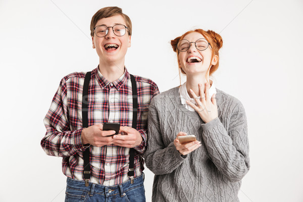 Laughing couple of school nerds using mobile phones Stock photo © deandrobot
