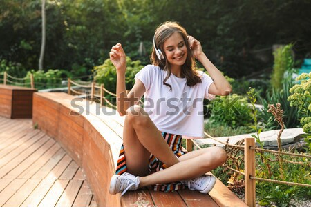Happy young girl drinking from a bottle with fizzy drink Stock photo © deandrobot