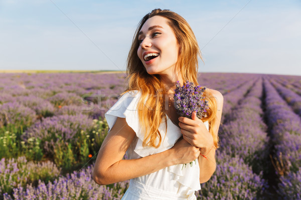 Stock photo: Photo of smiling joyful woman in dress holding bouquet with flow