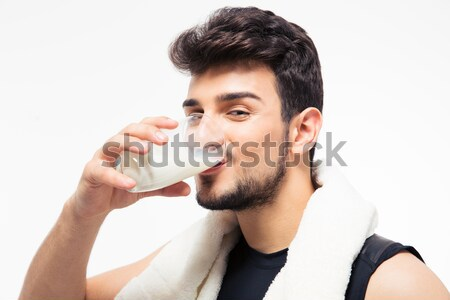 Smiling man spraying deodorant over gray background Stock photo © deandrobot