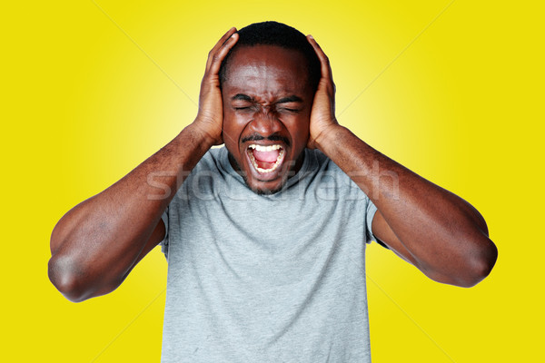 Portrait of african man shouting and closing ear by his hands on yellow background Stock photo © deandrobot