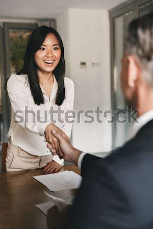 Smiling woman sitting at a business meeting with colleagues in office Stock photo © deandrobot