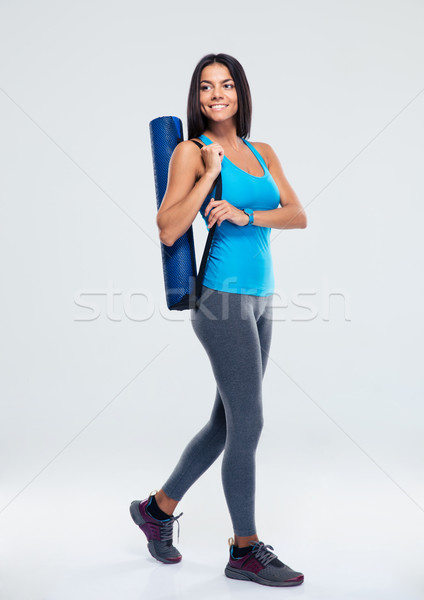 Smiling sports woman with yoga mat walking Stock photo © deandrobot