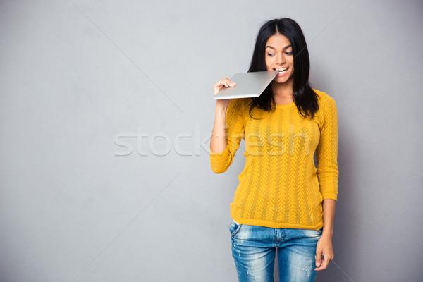Lezser nő harap táblagép szürke diák Stock fotó © deandrobot