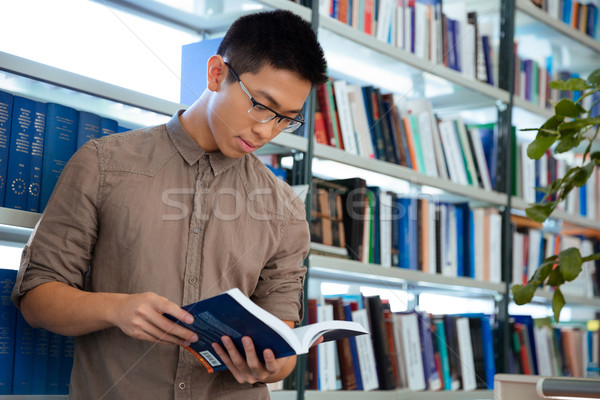 Asian man reading book in library  Stock photo © deandrobot