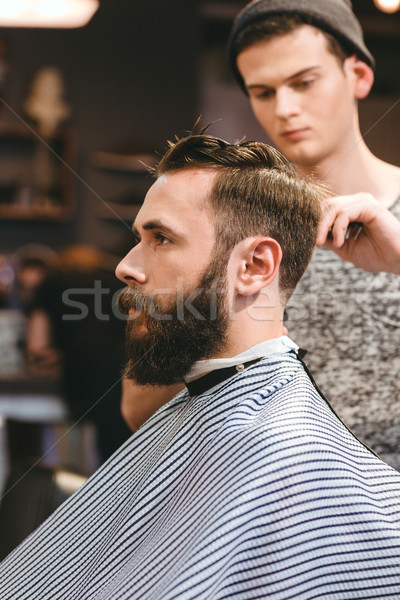 Professional hairdresser cutting bearded man's hair  Stock photo © deandrobot