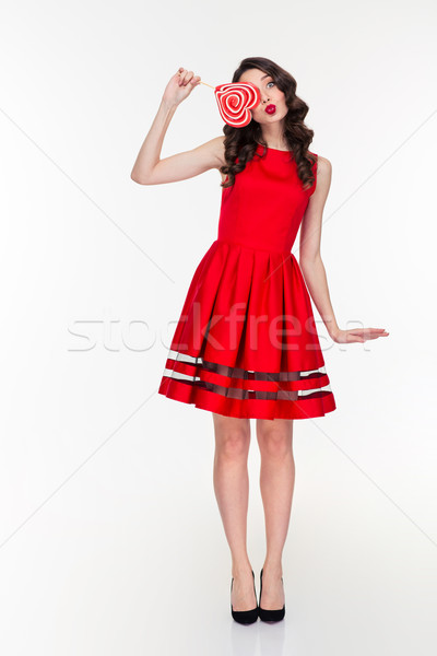 Cute funny amusing curly girl with heart shaped lollipop  Stock photo © deandrobot