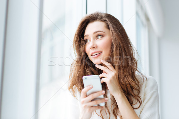 Woman holding smartphone and looking at window Stock photo © deandrobot