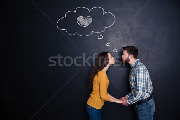 Happy couple holding hands and kissing over backboard background Stock photo © deandrobot