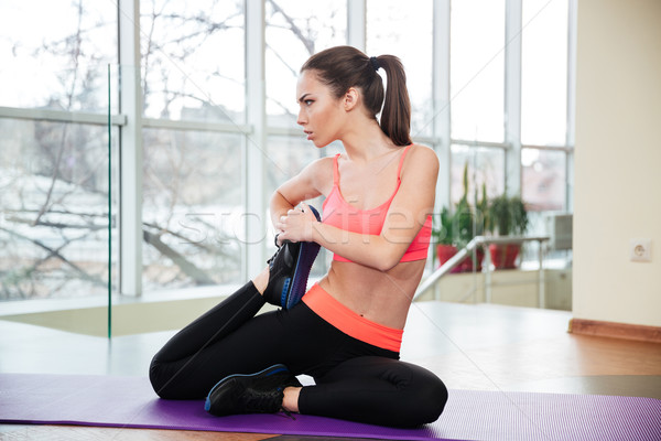 Sportswoman sitting on yoga mat and stretching legs Stock photo © deandrobot