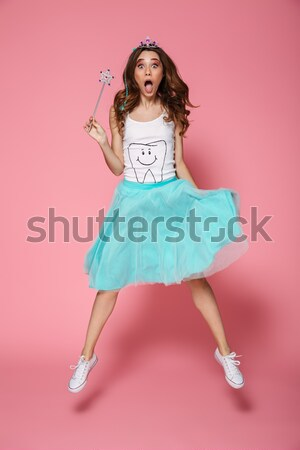 Stock photo: Charming happy young woman in bright pink skirt