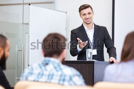 Cheerful speaker standing at the tribune in conference hall Stock photo © deandrobot