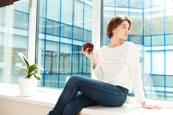 Attractive thoughtful young woman sitting on window sill in office  Stock photo © deandrobot