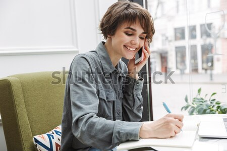 Female student doing her homework in cafe Stock photo © deandrobot