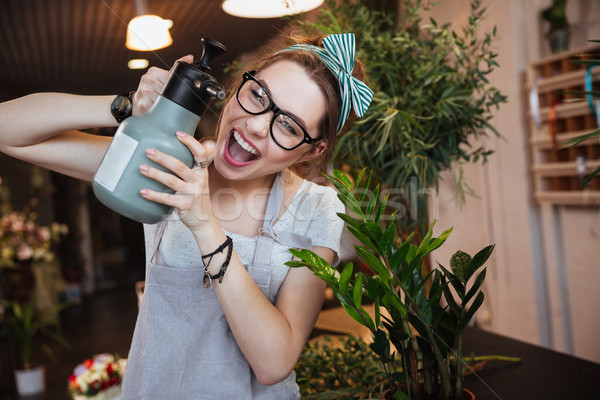 Woman florist with water sprayer watering flowers and shouting  Stock photo © deandrobot