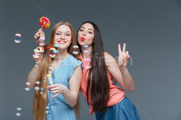 Kettő boldog játékos fiatal nők színes nyalóka Stock fotó © deandrobot