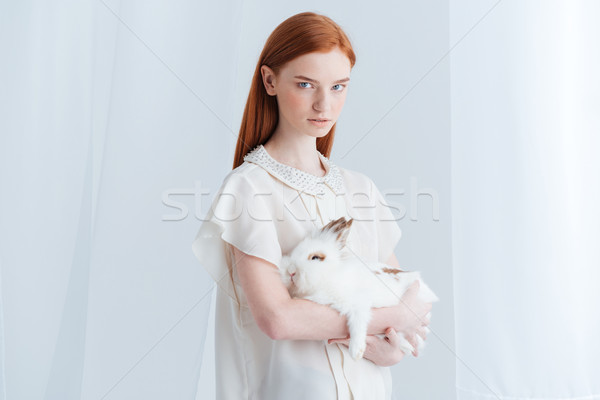 Serious redhead woman holding rabbit Stock photo © deandrobot