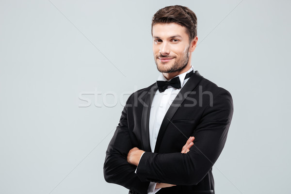 Smiling confident man in tuxedo standing with arms crossed Stock photo © deandrobot