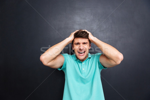Portrait of a crazy man shouting isolated over black background Stock photo © deandrobot