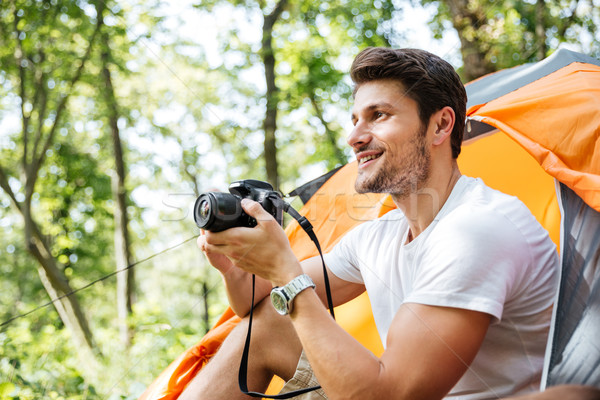 Man tourist sitting and using modern photo camera in forest Stock photo © deandrobot