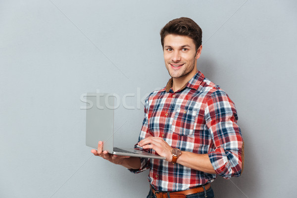 Happy young man in checkered shirt standing and holding laptop Stock photo © deandrobot