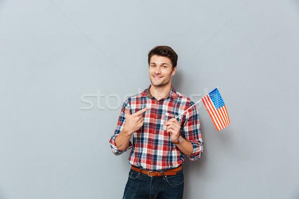 Mosolyog fiatalember mutat Egyesült Államok Amerika zászló Stock fotó © deandrobot