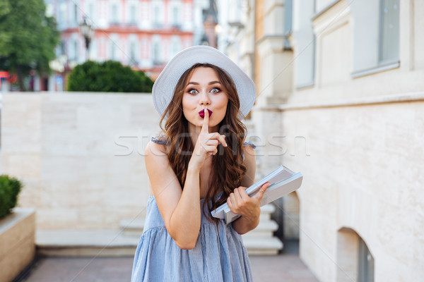 Young brunette woman showing silence sign with finger on lips Stock photo © deandrobot