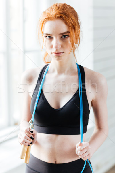 Fitness woman holding skipping rope at the gym Stock photo © deandrobot