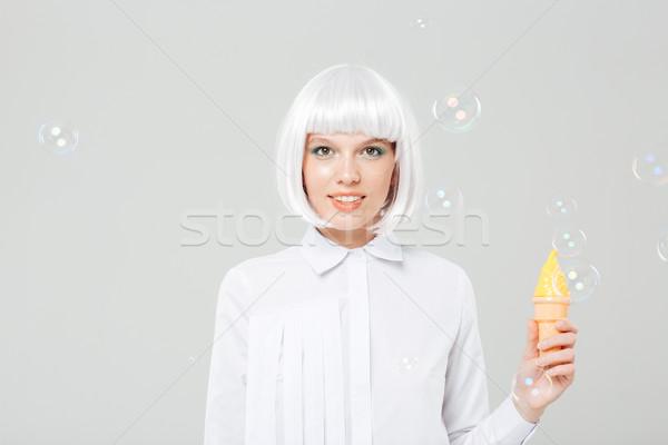 Mosolyog fiatal nő szőke nő paróka tart hamisítvány Stock fotó © deandrobot