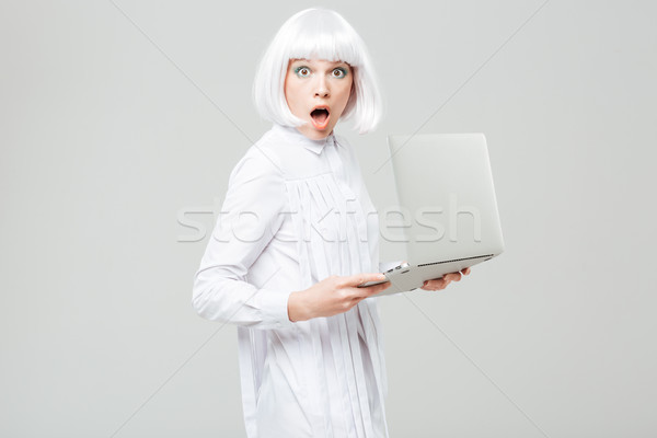 Surprised pretty young woman with opened mouth holding laptop Stock photo © deandrobot