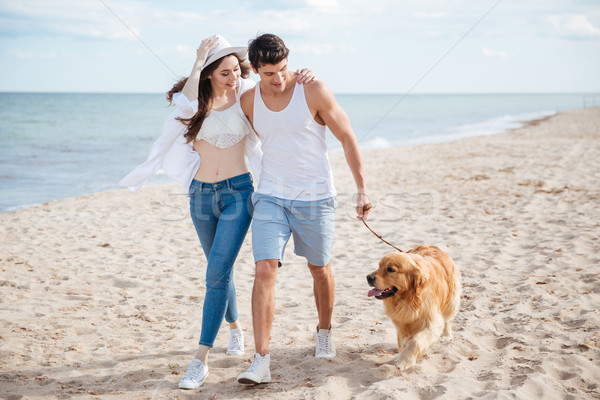 Young couple running along the beach with their dog Stock photo © deandrobot