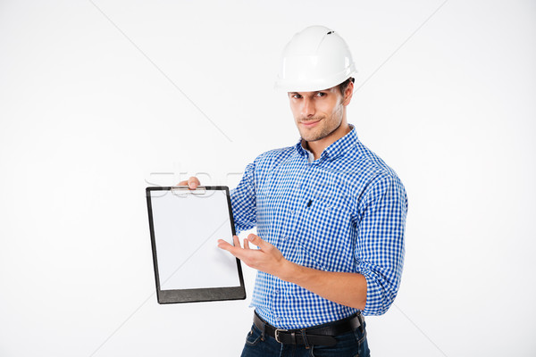 Man building engineer in hard hat pointing on blank clipboard Stock photo © deandrobot