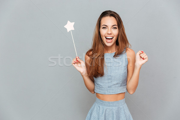 Happy amazed young woman holding magic wand Stock photo © deandrobot