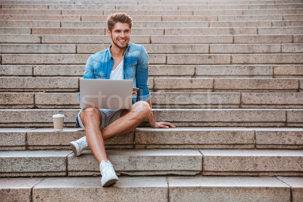 Man student with laptop sitting on the staircase Stock photo © deandrobot