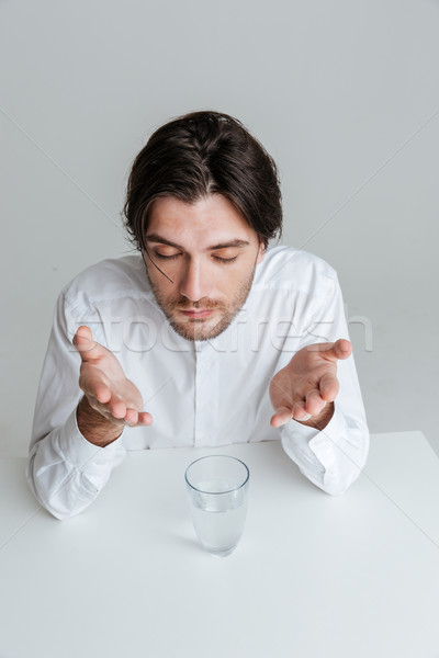 Man with eyes closed making hand gestures at the table Stock photo © deandrobot