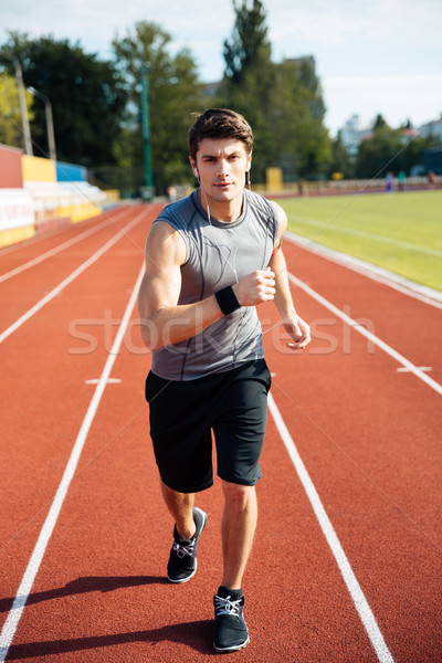 Concentrated sports man running down stadium track with earphones Stock photo © deandrobot