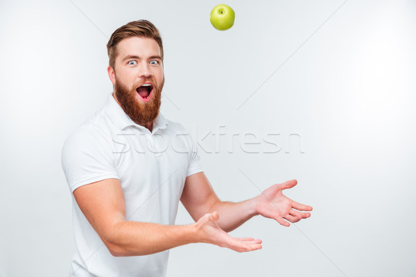 Portrait of handsome funnny bearded man throwing apple up Stock photo © deandrobot