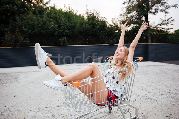 Happy smiling blonde woman having fun alone in shopping trolley Stock photo © deandrobot