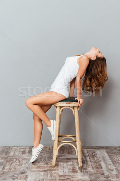 Portrait of a charming young woman posing on the chair Stock photo © deandrobot