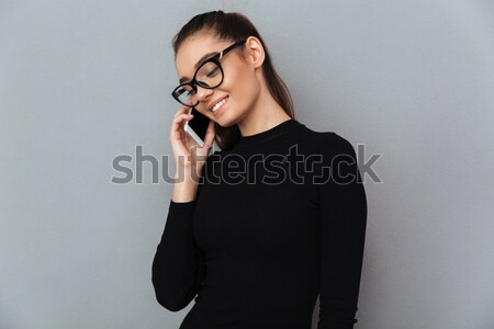 Gyönyörű barna hajú nő fekete ruha beszél mobiltelefon Stock fotó © deandrobot