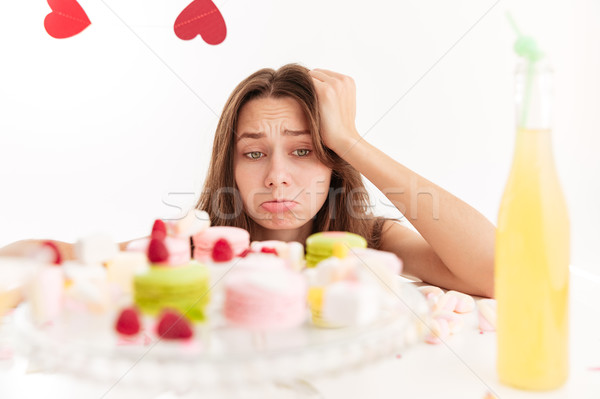 Sad upset young woman looking at sweests on the table Stock photo © deandrobot