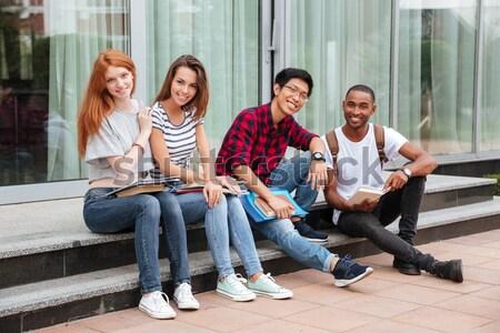 счастливым молодые люди сидят кампус вместе Сток-фото © deandrobot