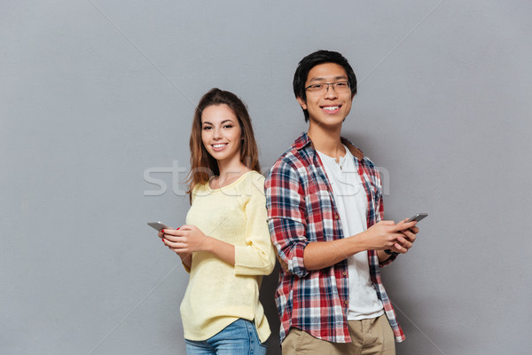 Portrait of a smiling couple standing and holding mobile phones Stock photo © deandrobot