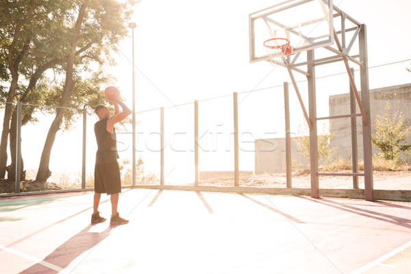 Basketball player practicing in the street with hoop Stock photo © deandrobot